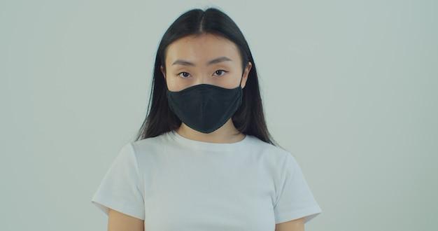Giovane bella donna asiatica che indossa maschera e cerca