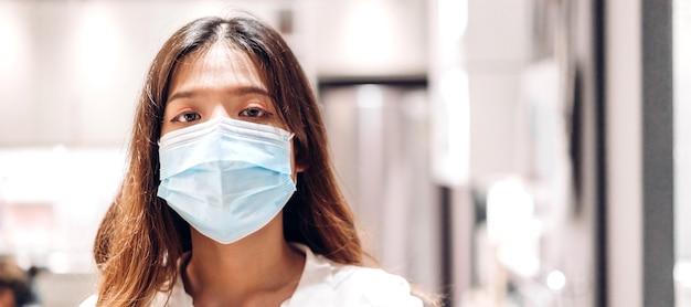 Giovane bella donna asiatica che indossa la maschera chirurgica per la protezione del viso con allontanamento sociale al concetto city.covid19