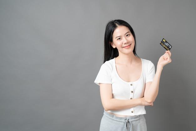 Giovane bella donna asiatica con la faccia felice e che presenta la carta di credito in mano mostrando fiducia e sicurezza per effettuare il pagamento
