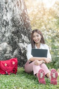 Giovane bella donna asiatica con la cuffia che tiene tablet, sorridendo e guardando la telecamera mentre era seduta sotto il grande albero al parco con la luce del sole.