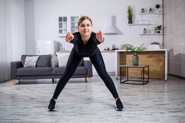 La giovane bella ragazza atletica in leggings e un top fa esercizi di stretching. uno stile di vita sano. la donna fa sport a casa.
