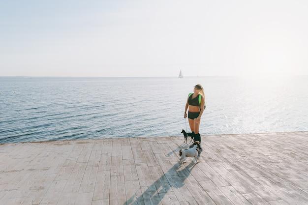 La giovane bella ragazza atletica con lunghi capelli biondi in abiti neri e due dei suoi cani che fanno sport all'alba in riva al mare