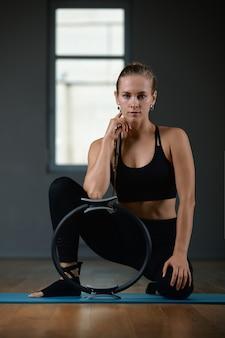 Una giovane, bella, donna atletica fa esercizi con un anello di pilates in palestra. mette in mostra la donna slava in un vestito nero.