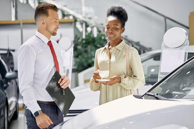 La giovane bella signora africana attraente beve una tazza di tè e ascolta attentamente l'agente di vendita professionale