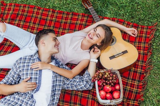 Giovane bella ragazza attraente con il suo ragazzo seduto sul tappeto coperta e godersi ogni momento