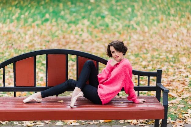 Giovane bella ballerina in cappotto giusto e scarpe da punta sedersi sulla panchina, riposare all'aperto nel parco di autunno