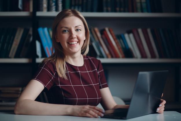 Giovane bella ragazza bionda dello studente di sorriso con la fine del computer portatile sul ritratto