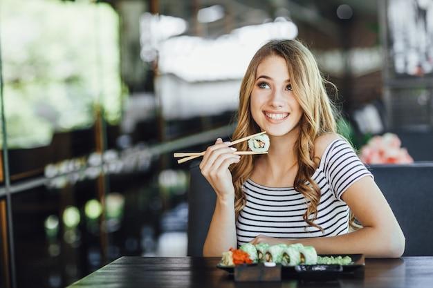 Una giovane bella donna bionda che mangia sushi sulla terrazza estiva di un ristorante giapponese