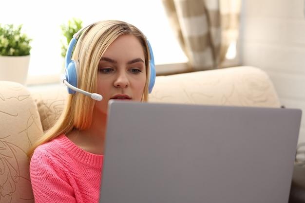La giovane bella donna bionda si siede sul sofà in soggiorno tiene il computer portatile tra le braccia ascolta la musica mattina soleggiata concept