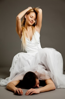 Giovane bella donna bionda in abito da sposa in piedi, tenendo l'uomo in biancheria intima da cravatta e guardandolo su sfondo grigio. giochi sessuali e pratica del concetto di bdsm