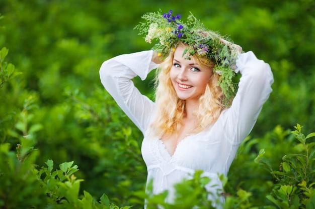 Giovane bella donna bionda in abito bianco e corona floreale in piedi e sorridente il giorno d'estate