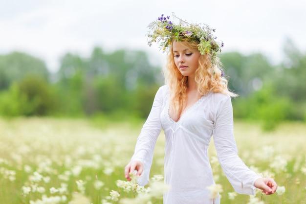 Giovane bella donna bionda in abito bianco e corona floreale