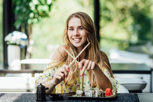 Una giovane bella donna bionda e carina che mangia sushi sulla terrazza estiva di un ristorante giapponese