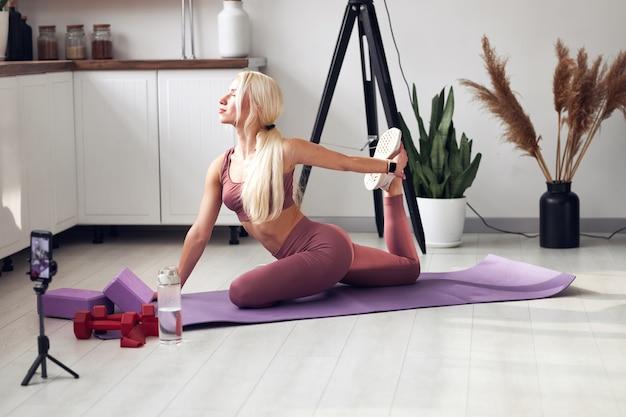 Giovane bella bionda si prende cura del suo corpo mentre è a casa durante la quarantena. allena le persone online tramite il suo telefono cellulare.