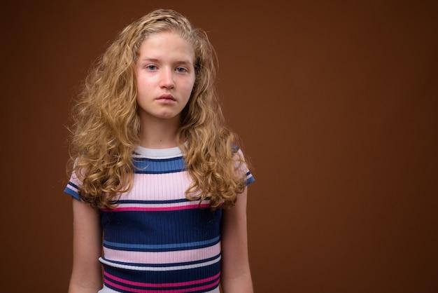 Giovane bella ragazza adolescente bionda su colore marrone