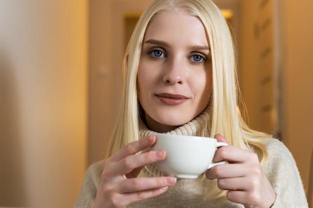 Una giovane e bella bionda con capelli sciolti, occhi azzurri e trucco naturale
