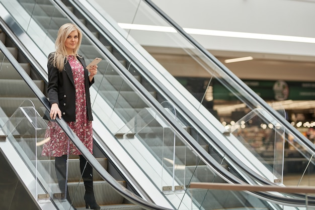 Giovane bella donna bionda in un abito su una scala mobile in un centro commerciale, con un telefono in mano