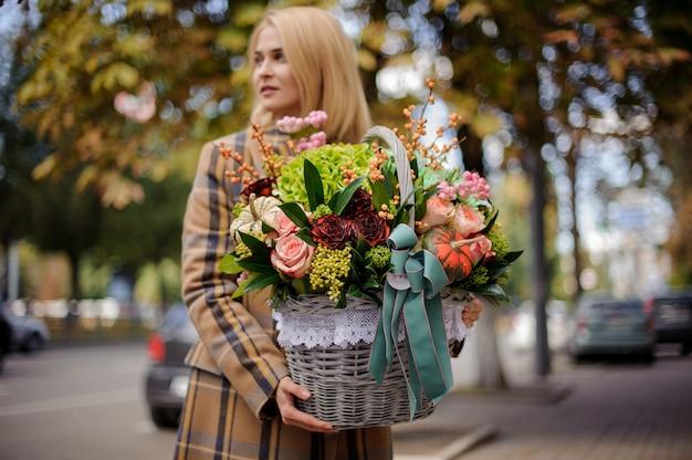 Giovane e bella donna bionda che tiene un grande cesto di vimini di fiori contro la città