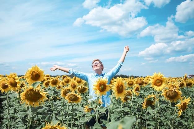 Giovane bella donna bionda in piedi nel campo di girasoli