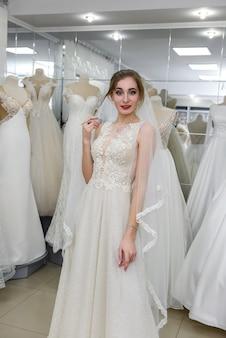Giovane bella sposa che sceglie vestito e velo in salone