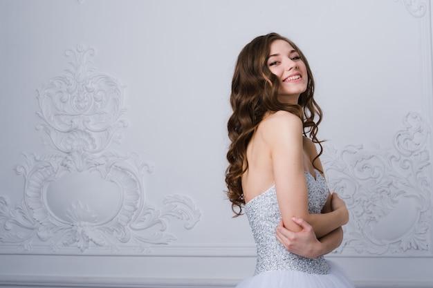 Giovane bella sposa che sta nella progettazione ornamentale interna antica fatta con modanature.