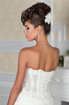 Giovane bella sposa in piedi torna alla telecamera in abito da sposa bianco