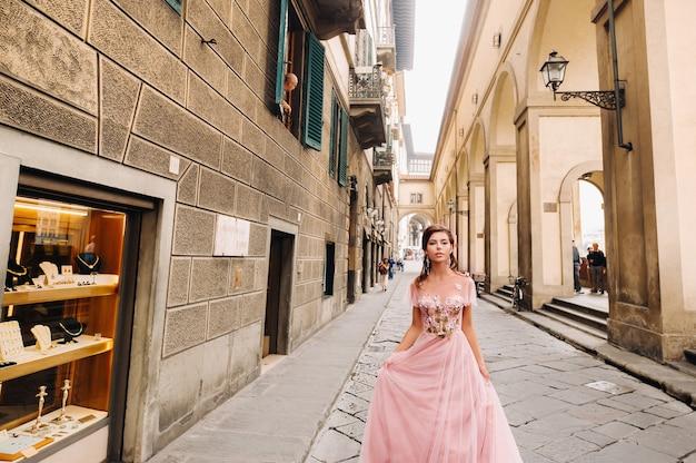 Una giovane bella sposa si trova al centro della città vecchia di firenze in italia.