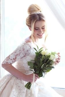 Giovane bella sposa. acconciatura da sposa, capelli biondi, abito da sposa, trucco e bouquet della sposa. tiro al coperto