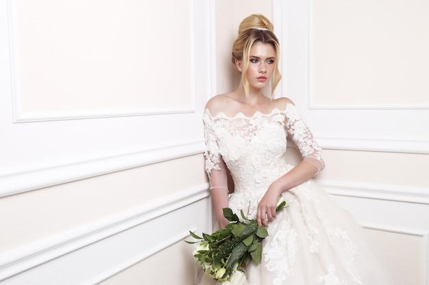 Giovane bella sposa. acconciatura da sposa, capelli biondi, abito da sposa, trucco e bouquet della sposa.