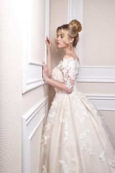 Giovane bella sposa. acconciatura da sposa, capelli biondi, abito da sposa, trucco. immagine interna