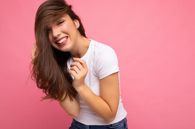 Giovane bella donna del brunet. signora alla moda in t-shirt bianca estiva casual per mock up. la femmina positiva mostra le emozioni sincere facciali. modello divertente isolato su sfondo rosa con spazio libero.