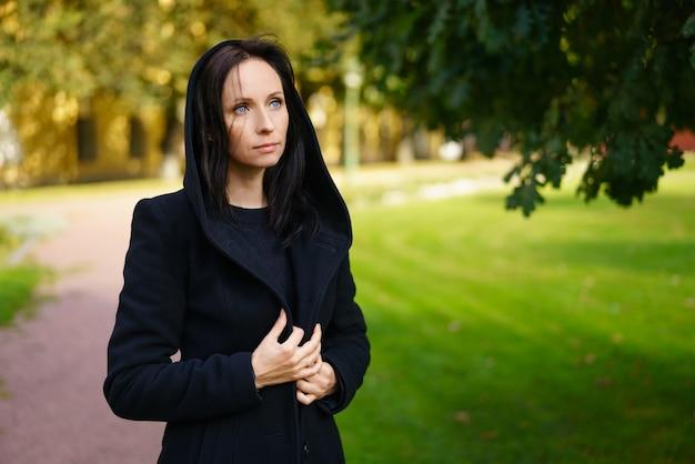 Una giovane, bella ragazza bruna in una giacca nera in posa sullo sfondo di un parco cittadino in una soleggiata giornata di primavera