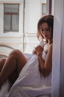 Una giovane bella ragazza castana in un hotel che si siede in una coperta sulla finestra