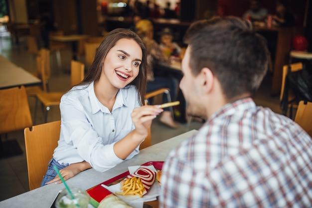 Giovane, bella ragazza bruna, sorridente, dà da mangiare a un ragazzo patatine fritte in un fast food bar
