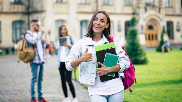 Ragazza giovane bella studentessa bruna in vestiti di jeans con zaino e libri in mano su un gruppo dei suoi amici studenti