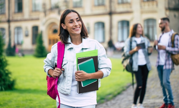 Ragazza giovane bella studentessa bruna in vestiti di jeans con zaino e libri in mano è in piedi su un gruppo dei suoi amici studenti