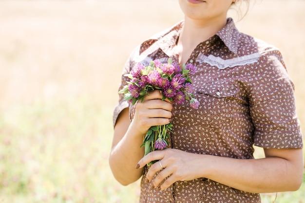 Giovane bella bruna con la treccia in testa in un abito in stile country sul campo