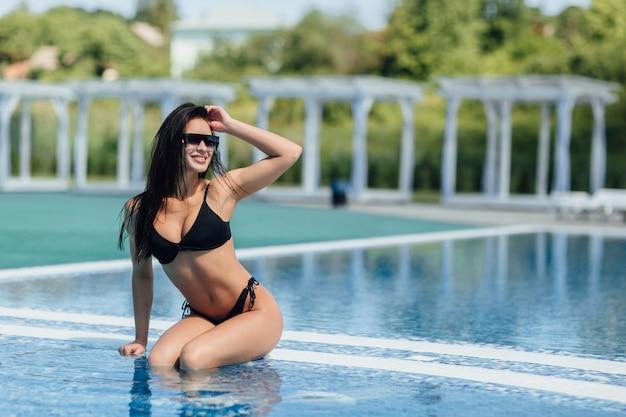 Modello di fitness giovane bella donna castana in costume da bagno nero e occhiali da sole pose in piscina in acqua.