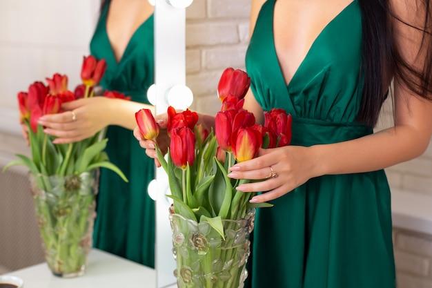 Giovane bella donna castana che tiene i tulipani rossi in vaso vicino allo specchio nel salone di parrucchiere