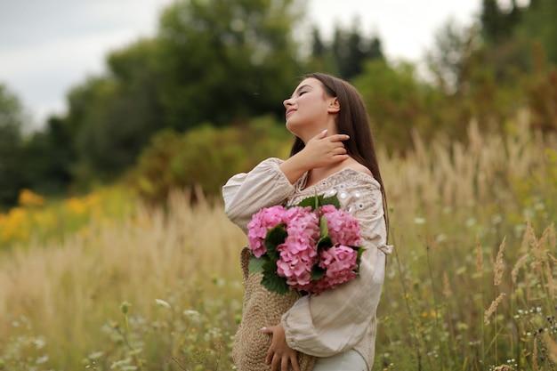Giovane bella donna castana sta tenendo il mazzo di fiori rosa ortensia in un sacchetto di paglia,
