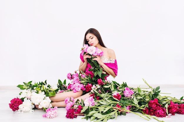 Modello di giovane bella donna bruna con bel trucco e capelli lunghi in peonie di colori rosa pink