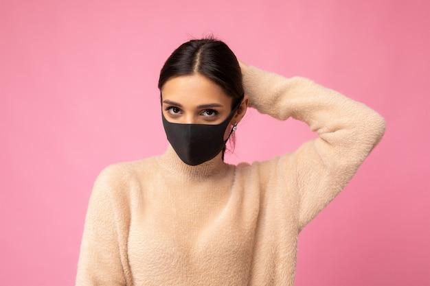 Giovane bella donna bruna in maschera protettiva riutilizzabile contro il virus sul viso contro il coronavirus isolato sulla parete di fondo rosa.