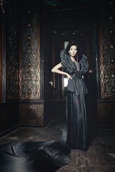 Giovane bella donna castana in piedi nella stanza del palazzo