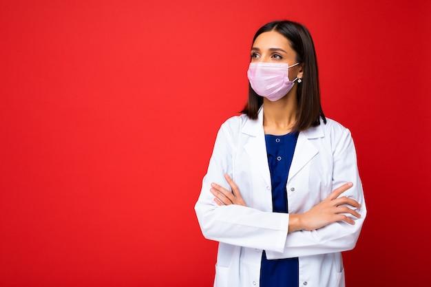 Giovane bella donna castana in maschera protettiva contro il virus sul viso contro il coronavirus e camice medico bianco isolato sullo sfondo. copia spazio