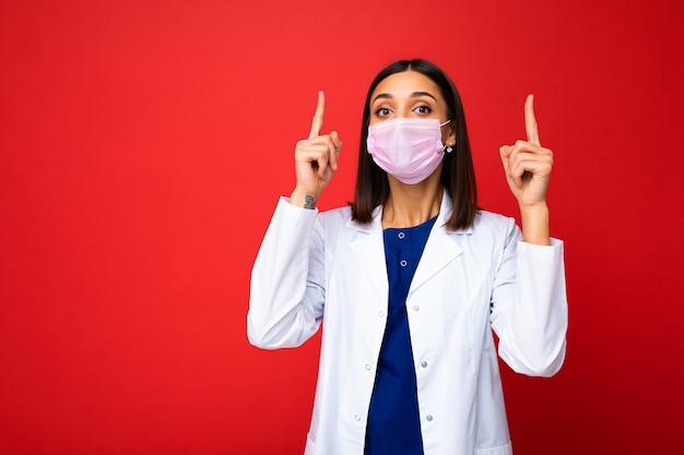 Giovane bella donna bruna in maschera protettiva antivirus sul viso contro il coronavirus e camice bianco medico isolato sullo sfondo e puntando le dita verso l'alto.