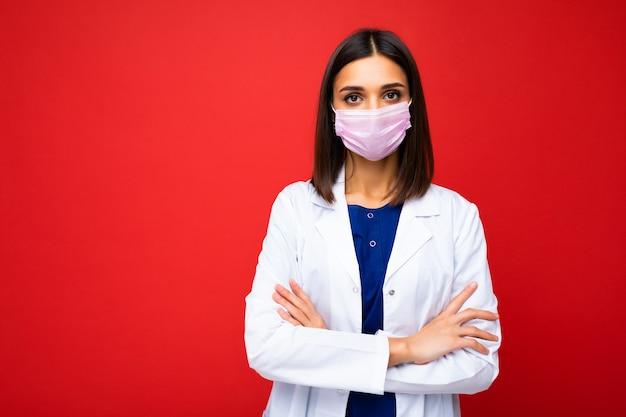 Giovane bella donna bruna con maschera protettiva da virus sul viso