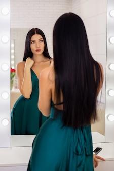 Giovane bella donna castana con capelli lunghi che esamina lo specchio nel salone di parrucchiere