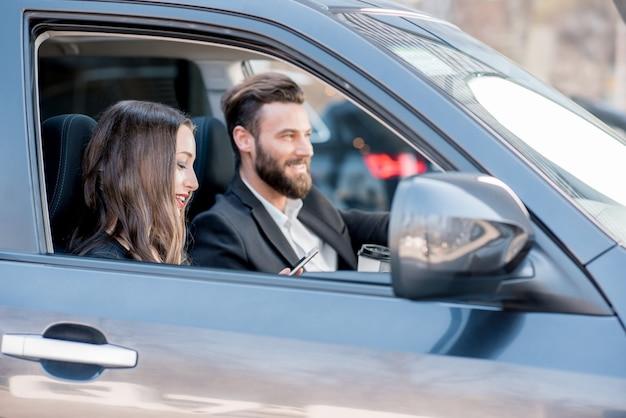 Giovane bella coppia di affari alla guida di un'auto in città