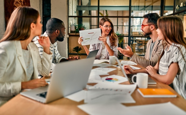 Giovane bella donna d'affari in bicchieri mostra un grafico su carta a un gruppo di colleghi seduti a un tavolo con i laptop in un ufficio moderno.