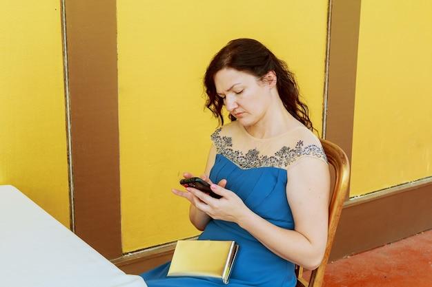 La giovane e bella donna d'affari scrive un messaggio sul suo cellulare per strada in estate. nelle mani di orologi intelligenti.
